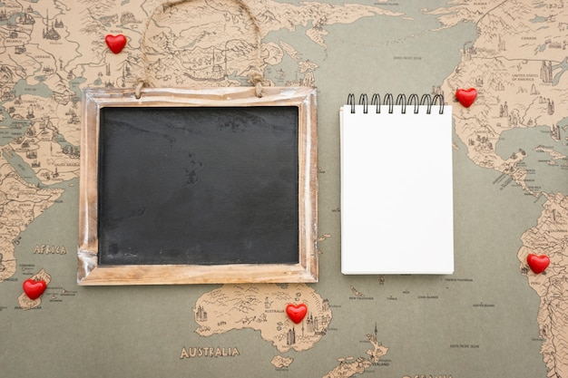 Vintage world map background with slate and notebook