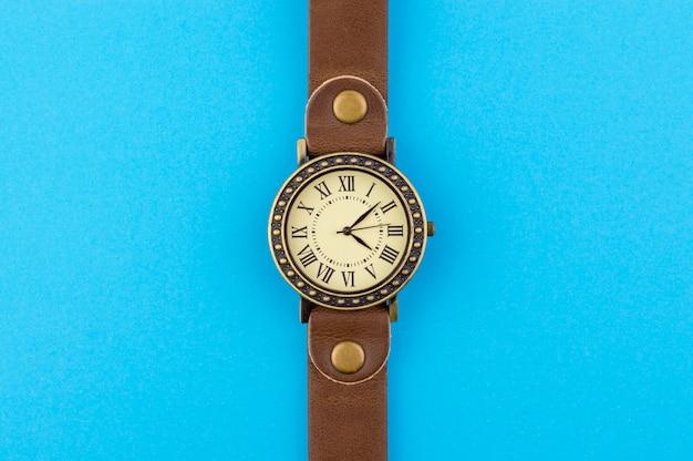 Vintage wrist watch on blue background