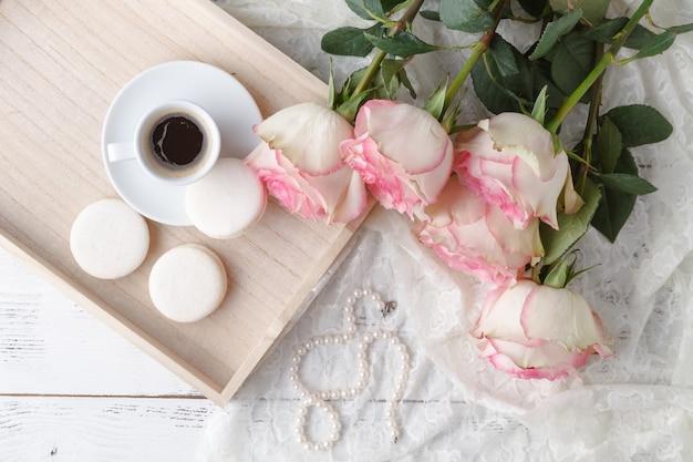 Чашка кофе, блокнот и розовые цветы. vintage.