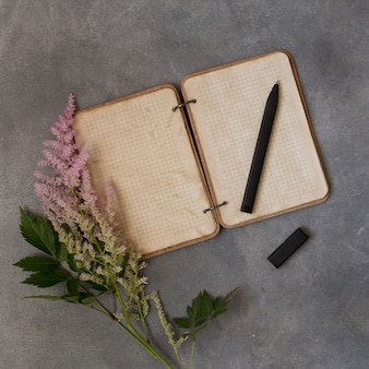 Квартира взгляд сверху кладет пустой блокнот с розовыми цветками, пестротканую астильбу, модель-макет на серую предпосылку. текстовое пространство. vintage. приглашение на свадьбу или день рождения или концепция сообщения