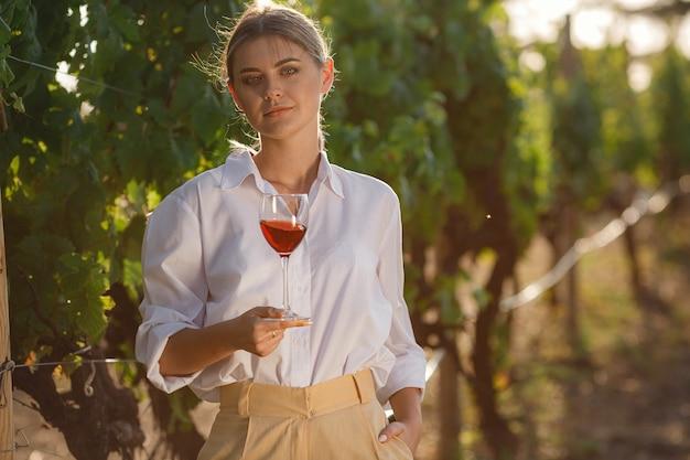 Виноделка дегустирует красное вино из бокала в винограднике. фон виноградников на закате.