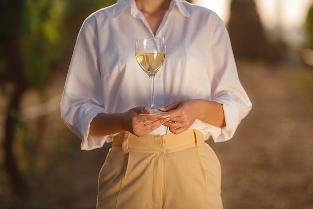 포도밭에서 유리에서 화이트 와인을 시음하는 양조 여자
