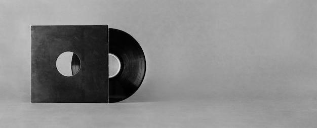 추상 회색 배경에 고립 된 검은 종이 봉투에 비닐 오디오 디스크