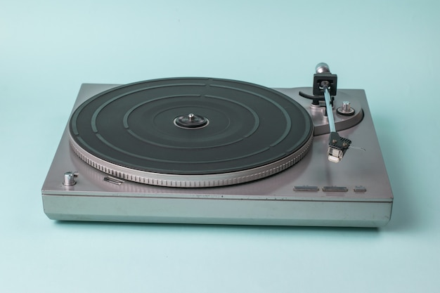 Vinyl disc player without disc on blue. retro equipment for playing music.
