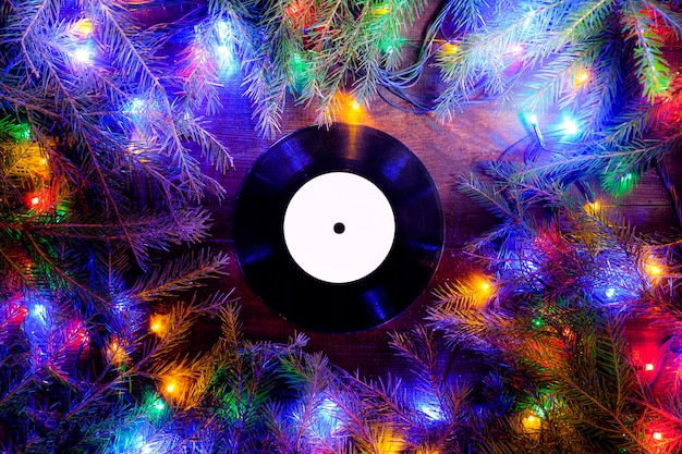 Vinyl gramophone record in christmas style for christmas playlist flat view with christmas lights