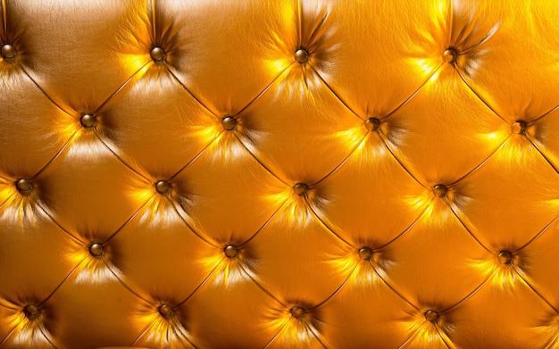 金色の背景にビニールまたは革張りのパッド入り素材。家具、装飾、デザインコンセプト。家具、装飾、デザインコンセプト。