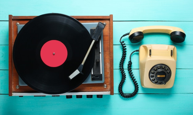 Vinyl player, rotary phone. old-fashioned objects on a blue wooden background. retro style, 70s. top view.