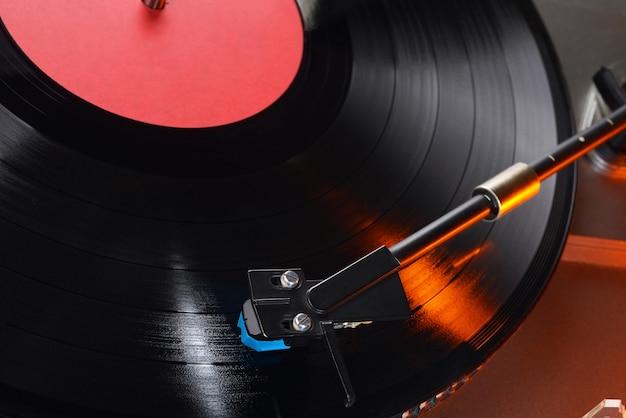 ロングプレイまたはlpレコードのクローズアップショットを備えたビニールプレーヤーのトーンアーム。