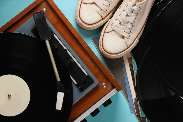 Vinyl player with vinyl record albums, retro sneakers on blue