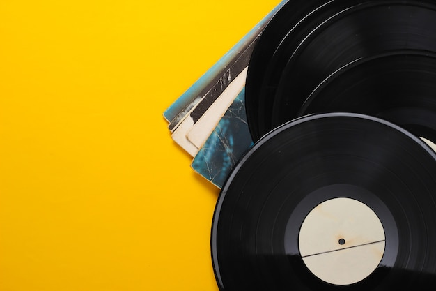 Vinyl record albums isolated on yellow.
