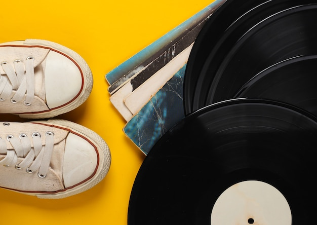 Vinyl record albums and retro sneakers on yellow