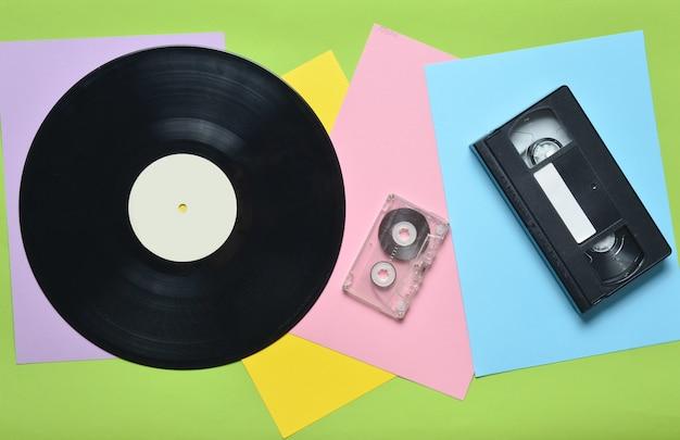多色紙の壁にビニールレコード、オーディオカセット、ビデオカセット。レトロなスタイル。上面図