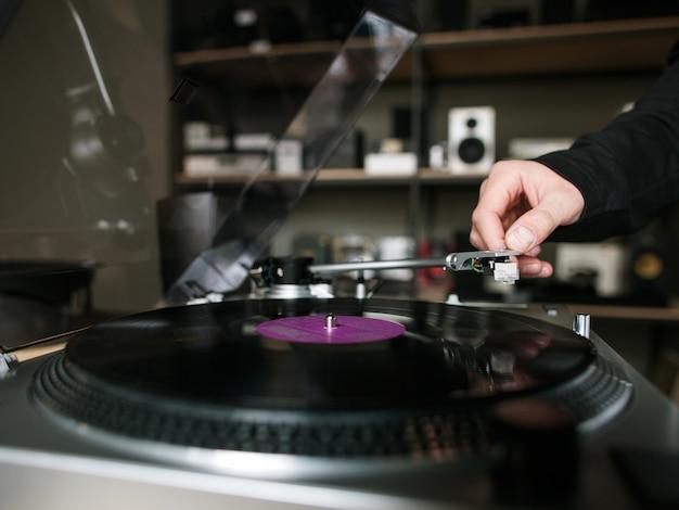 비닐 레코드 근접 촬영입니다. 레트로 뮤지컬 가게. 음악을 듣고 인식 할 수없는 남성, 현대적인 턴테이블