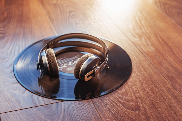 Vinyl record and headphone over wooden table. audio enthusiast,music lover or professional disc jockey equipmen.