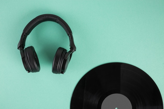 Vinyl record and headphones on abstract pastel background