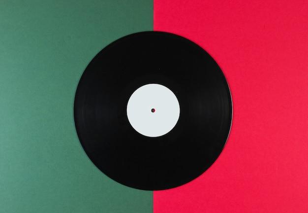 Виниловая пластинка на зелено-красной поверхности. ретро стиль.
