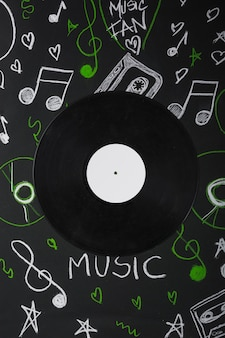 Vinyl record over the blackboard with drawn musical notes