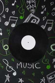 Виниловая пластинка над доской с нарисованными музыкальными нотами