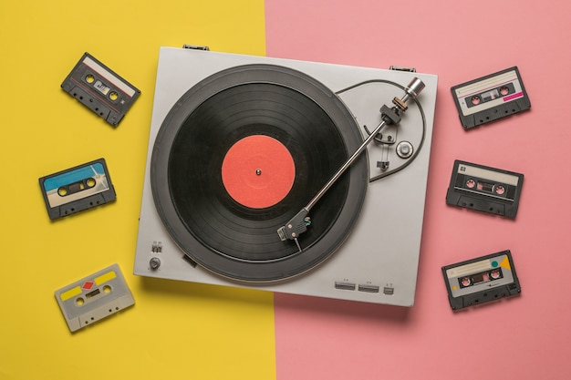Vinyl record player and tape recorders on a yellow and pink background.