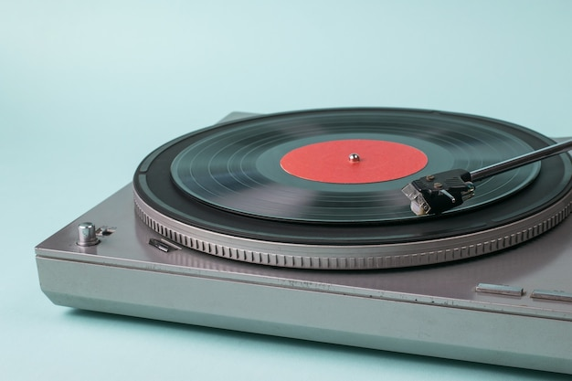 Vinyl record player with a red disc on blue. retro equipment for playing music.