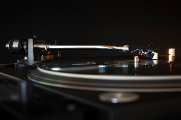 Vinyl record spinning on modern turntable. black background. space for text. play music concept.