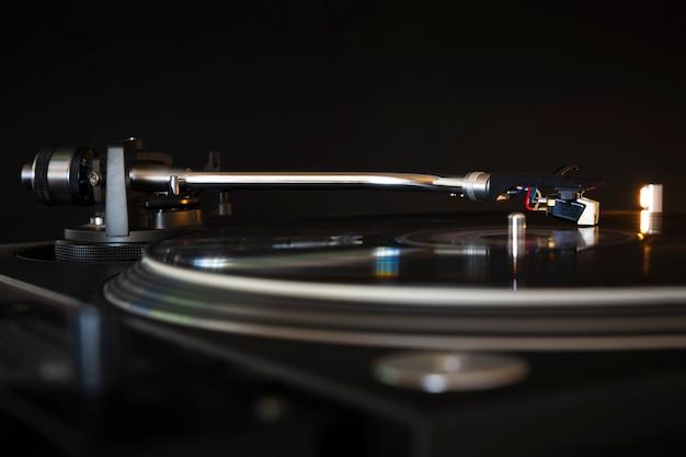 Виниловая пластинка крутится на современном вертушке. черный фон. место для текста. слушайте музыкальную концепцию.