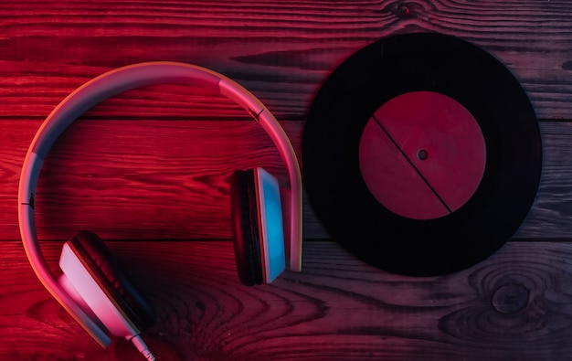 Vinyl record, stereo headphones on wooden surface. neon red and blue light