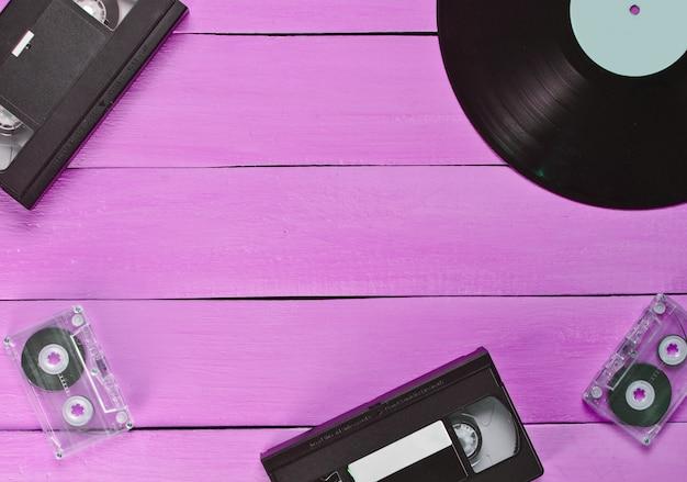 Виниловая пластинка, видеокассета, аудиокассета на розовом деревянном фоне
