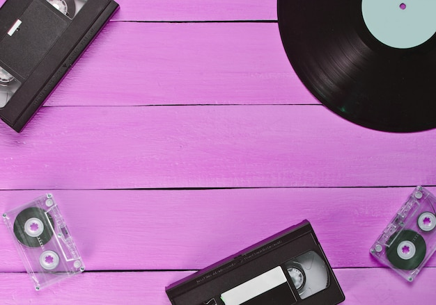 Vinyl record, video cassette, audio cassette on a pink wooden background