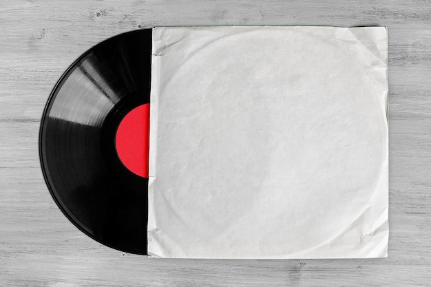 Vinyl record in a white paper envelope lying on a wooden table