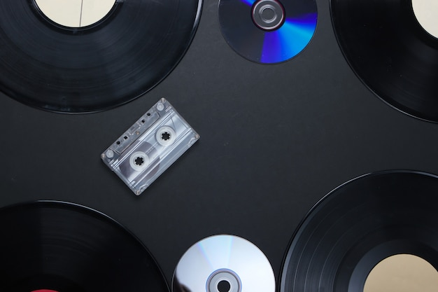 Vinyl records, audio cassette and cd discs on black surface