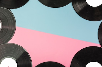 Vinyl records border on dual blue and pink background