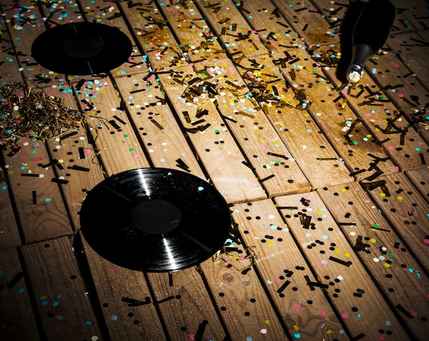Vinyl records and bottle of drink between confetti