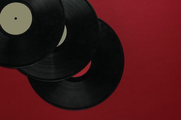 Виниловые пластинки на красном фоне. вид сверху