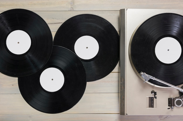 Vinyl records and turntable vinyl record player on wooden table