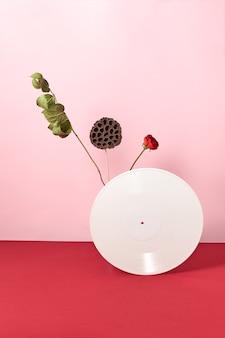 Виниловая белая ретро-пластинка, украшенная сухими ветками и красным цветком