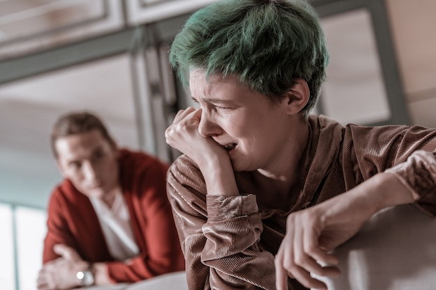 Violent argument. young green-haired girlfriend crying after emotional and violent argument