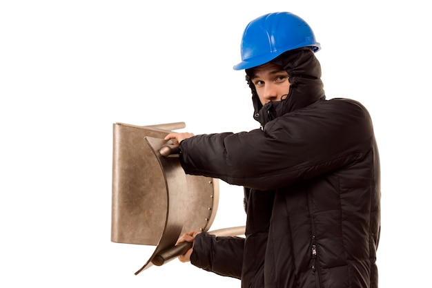 Violent teenage hooligan in a hoodie and hardhat brandishing a wooden chair