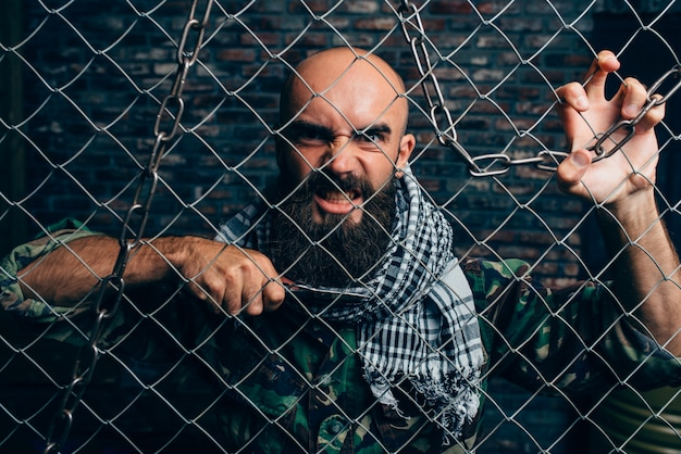Violent terrorist with knife against metal grid