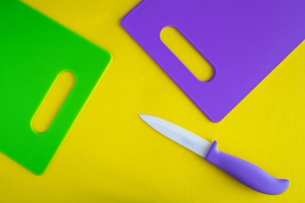 黄色の表面に紫と緑のまな板。上面図。