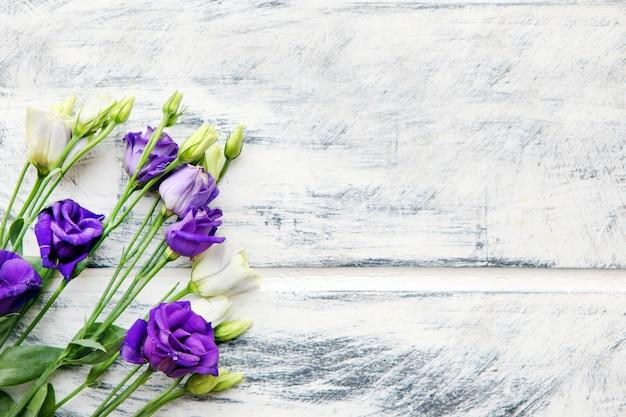 白く塗られた木製の背景に紫と白のトルコギキョウの花。テキスト用のスペースをコピーします。花の背景デザイン。切り花lisianthusまたは草原リンドウの美しい植物の背景。