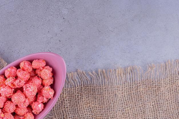 대리석 배경에 풍미있는 팝콘의 작은 봉사로 가득한 보라색 그릇. 고품질 사진