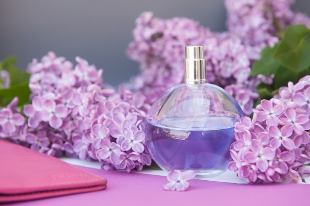 Violet color circle perfume bottle, presentation of perfume with lilac flowers