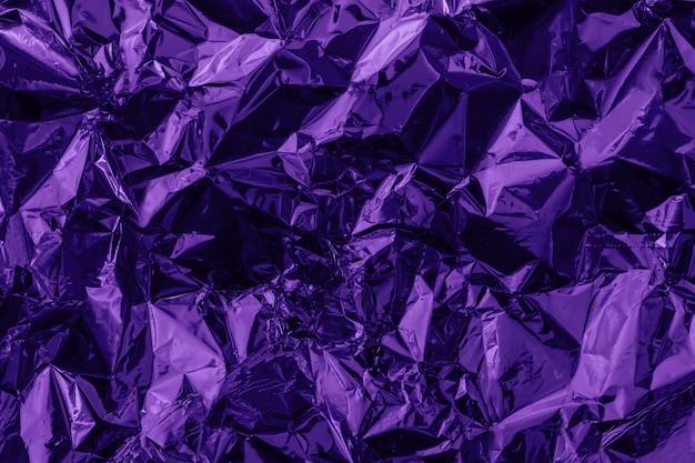 Violet deformed background made of tinted foil