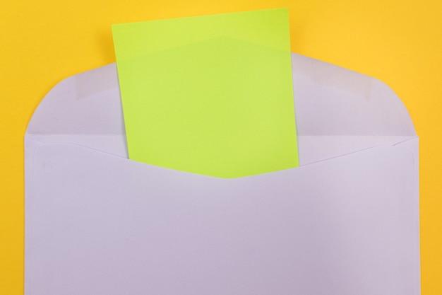 Фиолетовый конверт с чистым зеленым листом бумаги внутри