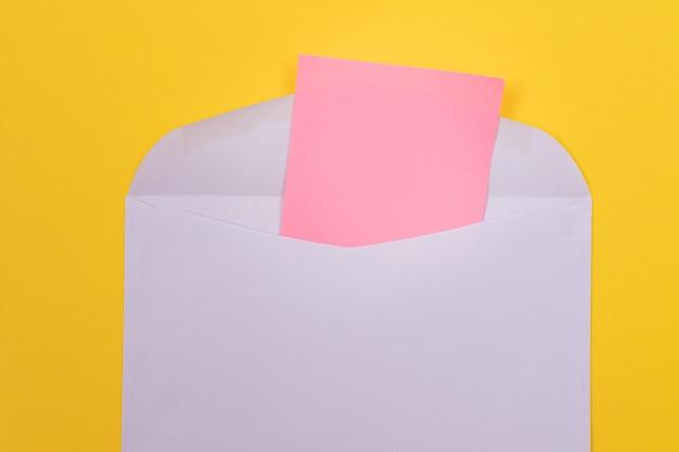 Фиолетовый конверт с чистым розовым листом бумаги внутри