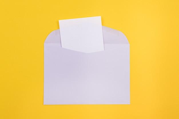 Фиолетовый конверт с чистым белым листом бумаги внутри
