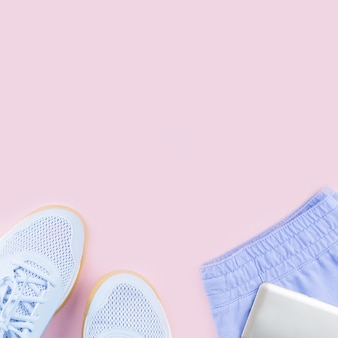 Violet female sneakers, running shorts and smartphone on pink background. flat lay, copy space.