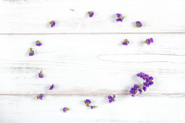 Violet flowers frame composition on a rustic white wooden background