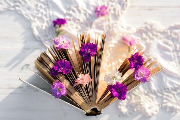 本の上の紫の花gelichrysum。木製の古いテーブルの上に透かし編みのテーブルクロス。村での夜。屋外の夕日、バタニカ、ガラスの美しい花。